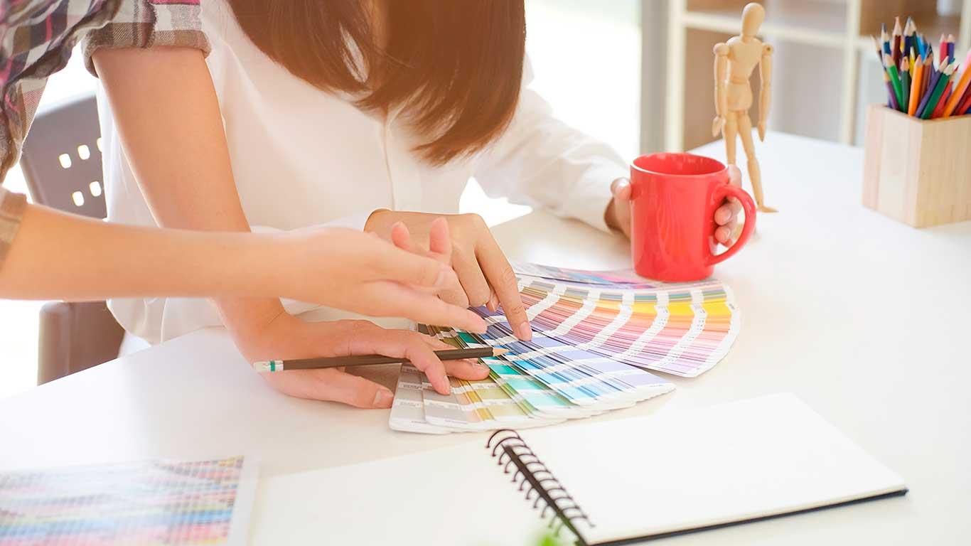 doua colege se uita intr-un paletar de culori, pentru a stabili culorile ce vor fi folosite in design-ul final al unei invitatii de nunta