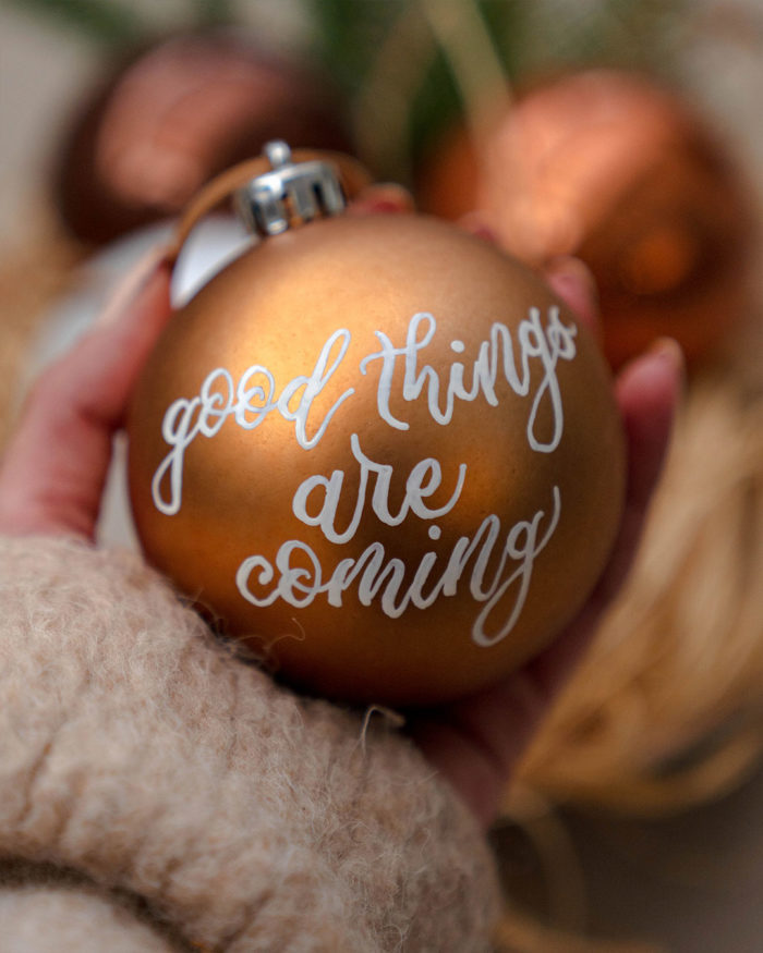 "mana ce tine un glob de plastic cu aspect mat caligrafiat manual cu citat ""good things are coming"""